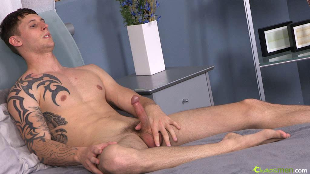 Tattooed guy is relaxing by stroking his bushwa
